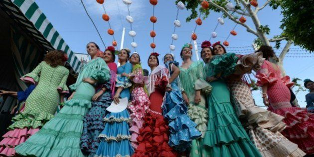 SEVILLE, SPAIN - APRIL 21: Women wearing the traditional flamenco dresses, often in bright colors, and...