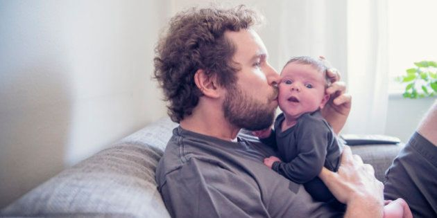 Young bearded dad kissing his 10 days newborn baby while relaxing on a couch at home. Both are wearing...