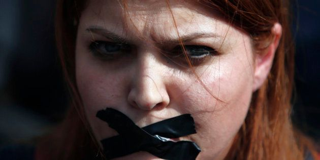 A woman places a bandage other mouth as she protests Saturday's explosions in Ankara, Turkey, Tuesday,...