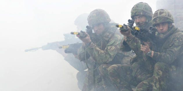 OKSBOL, DENMARK: Soldiers from the British Royal Marines Commando demonstrate city fighting techniques...