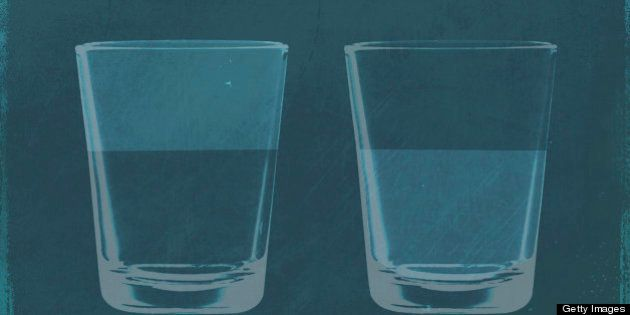 A half full glass of water next to a half empty glass of