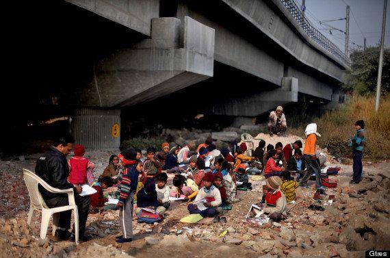 Un grupo de niños de la India dan clase debajo de un puente en plena ola de frío