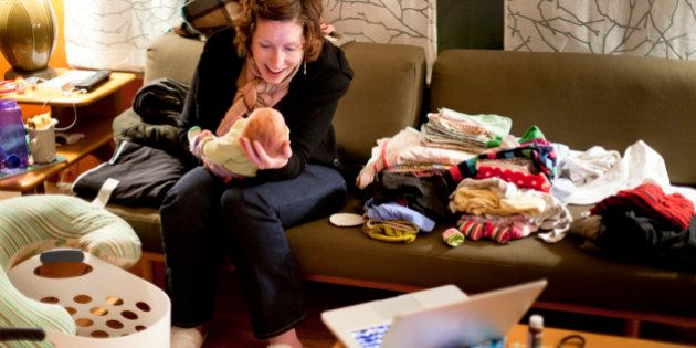 A smiling mother with red hair plays with her baby on a couch amid piles of messy laundry at night in...