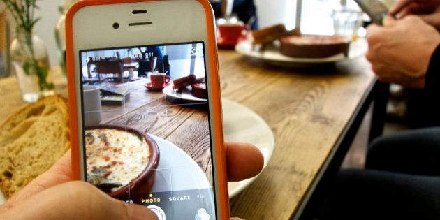 Two people photographing their food in a café with their