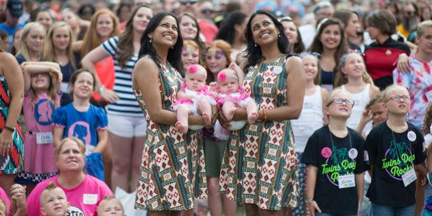 Sets of identical twins and multiples smile for a camera in the air taking a group photo of all the twins...