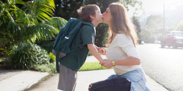Boy kissing mother goodbye walking to