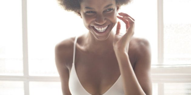 Smiling woman in bra standing by