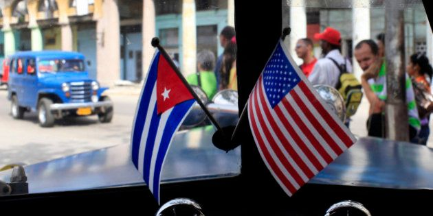 Miniature flags representing Cuba and the U.S. are displayed on the dash of an American classic car in...