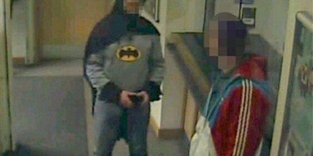 Un hombre vestido de Batman entrega a un delincuente en una comisaría