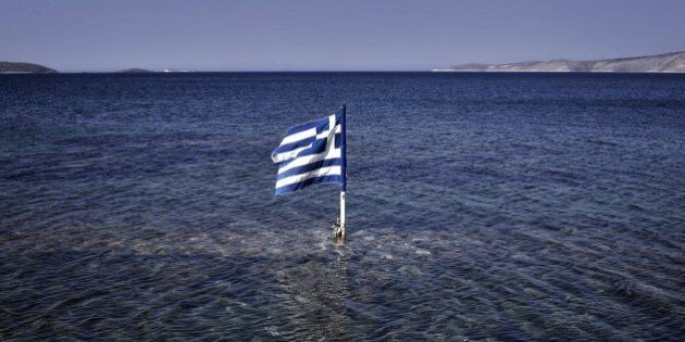 This photo taken on July 29, 2015 shows a Greek flag floating in the sea at the Kalamitsa beach on Skyros...