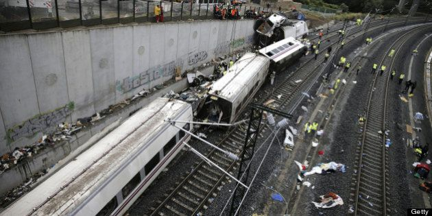 Rescuers, forensics and police officers work at the site of a train accident near the city of Santiago...