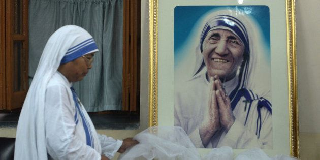 TOPSHOT - A nun of ?the Missionaries of Charity decorates a picture of Mother Teresa prior to a special...