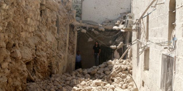 Residents inspect their damaged homes after an airstrike on the rebel-held Old Aleppo, Syria August 15,...