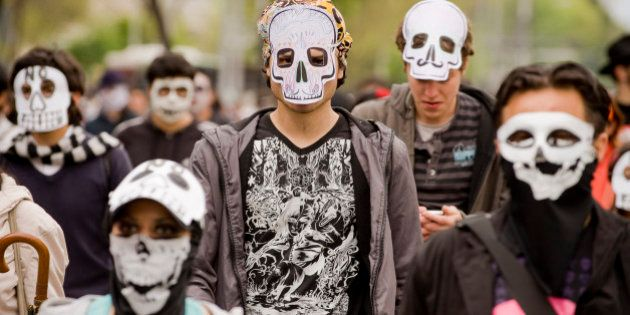 People wearing masks of skulls protest against violence in the country, in Mexico City on November 27,...