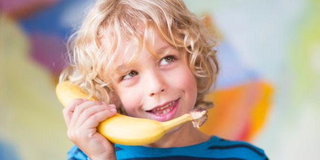 SANKT AUGUSTIN, GERMANY - AUGUST 05: Portrait of a six-year-old boy with blond curls talking on the banana...