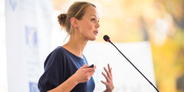 Pretty, young business woman giving a presentation in a conference/meeting setting (shallow DOF; color...