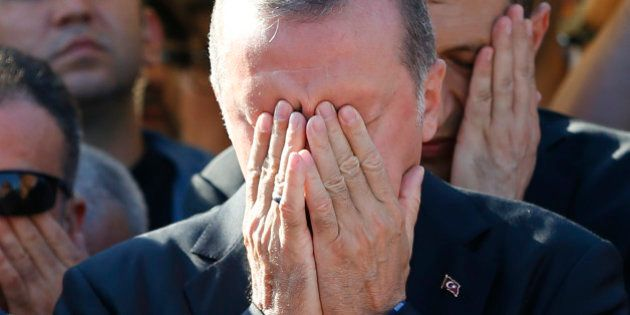 Turkish President Recep Tayyip Erdogan prays during a funeral service for a victim of the thwarted coup...