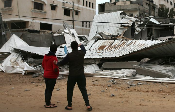 Palestinians inspect a damaged building that belonged to the Hamas ministry of prisoners.
