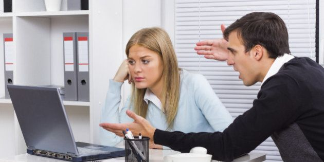 Businessman is sitting in office with his secretary and he is very angry at her because of