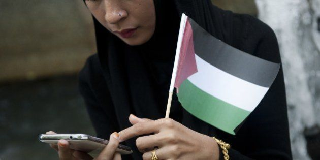 A protestor check her phone as she holds a Palestinian flag outside the Israeli embassy in Bangkok, during...