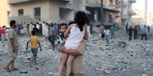 A man carries two children away from the scene of an explosion in the northern Syrian city of Raqqa,...