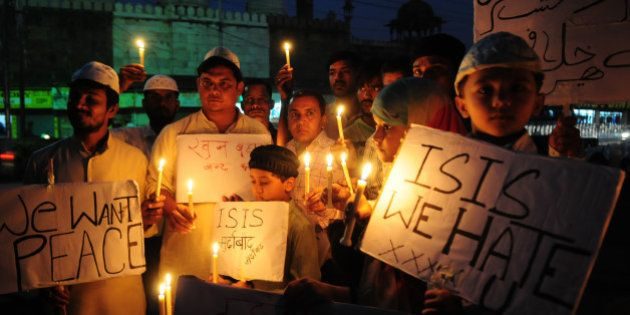 BHOPAL, INDIA - NOVEMBER 15: Muslim kids hold placards with slogans against the ISIS during a candle...