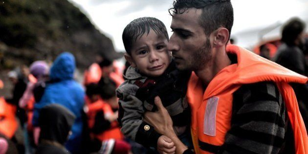 A man holds a young boy after they arrived with other refugees and migrants on the Greek island of Lesbos...