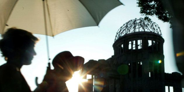 Japanese women walk past the gutted A-bomb dome in Peace Memorial Park in Hiroshima, Japan August 6,...