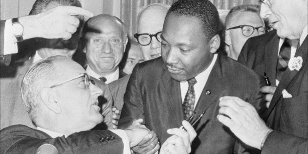 (FILES) US President Lyndon Johnson (l) shakes hands with the US clergyman and civil rights leader Martin...