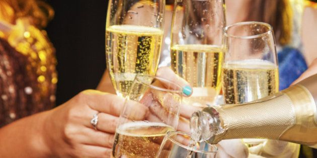 Five hands holding five champagne flutes being clinked together while being filled with champagne from...