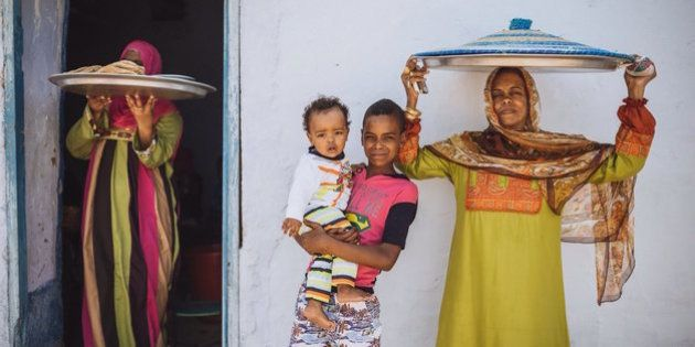 Relatives and neighbors of the groom's mother helping her in cooking and delivering the food for...