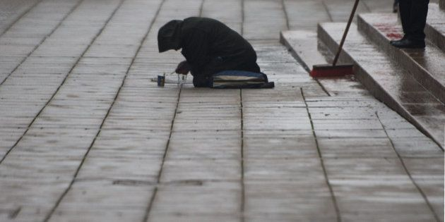 A beggar kneels on the ground as a man sweeps away rubbish from new year's celebrations in Stuttgart,...