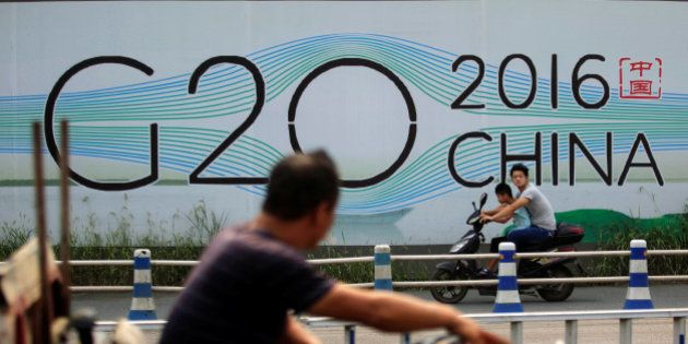 People cycle past a billboard for the upcoming G20 summit in Hangzhou, Zhejiang province, China, July...