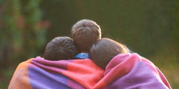 Siblings wrapped in blanket in