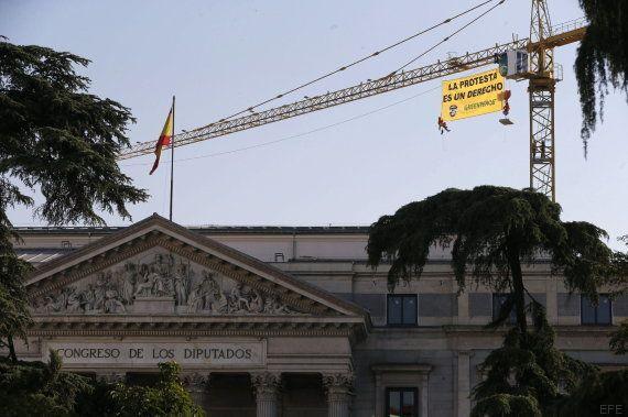 Greenpeace se sube a una grúa sobre el Congreso en protesta contra la 'Ley
