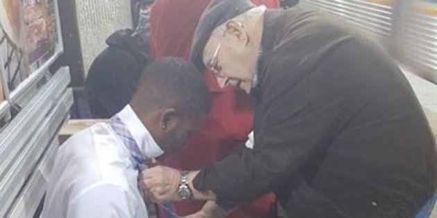 Un anciano enseña a un joven a hacerse el nudo de corbata en el