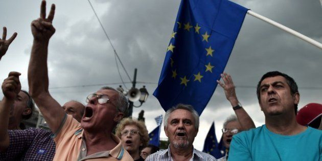 Pro-euro protesters hold European Union flags during a demonstration in front of the parliament in Athens...