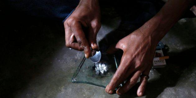 A heroin addict prepares heroin before using it in Lamu November 21, 2014. Picture taken November 21,...