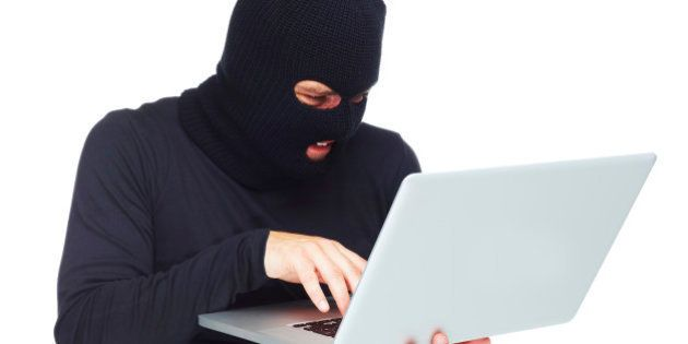 A studio concept shot of a masked thief holding a laptop isolated on