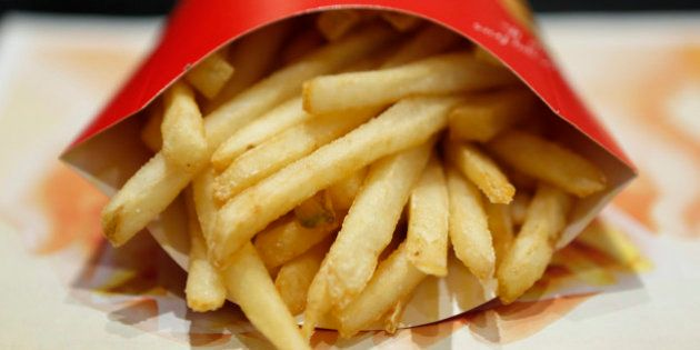 A packet of french fries sit on a tray in this arranged photograph at a McDonald's restaurant, operated...