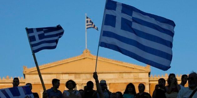 Supporters of the No vote wave Greek flags after the referendum's exit polls at Syntagma square in Athens,...