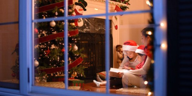 Mother reading to her daughters in front of fireplace and Christmas tree. Pictured from outside of