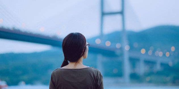 A rear view of a young woman looking away to the sea during sunset, with illuminated Tsing Ma Bridge...