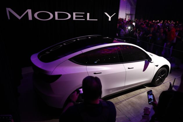 Attendees take photographs of the Tesla Inc. Model Y crossover electric vehicle during an unveiling event...