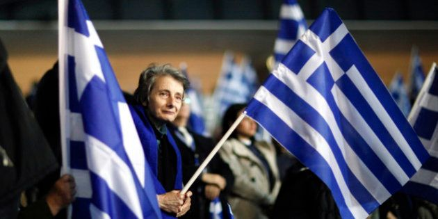 A supporter of the New Democracy party holds the Greek national flag during a pre-election rally by the...