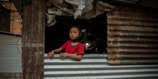 KATHMANDU, BHAKTAPUR - APRIL 24: A girl in an open window of a typical metal sheet temporary shelter...