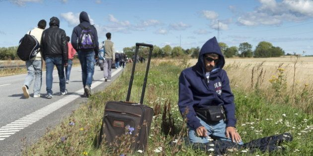 A migrant prays beside a freeway north of Rodby as a large group of migrants, mainly from Syria, walk...