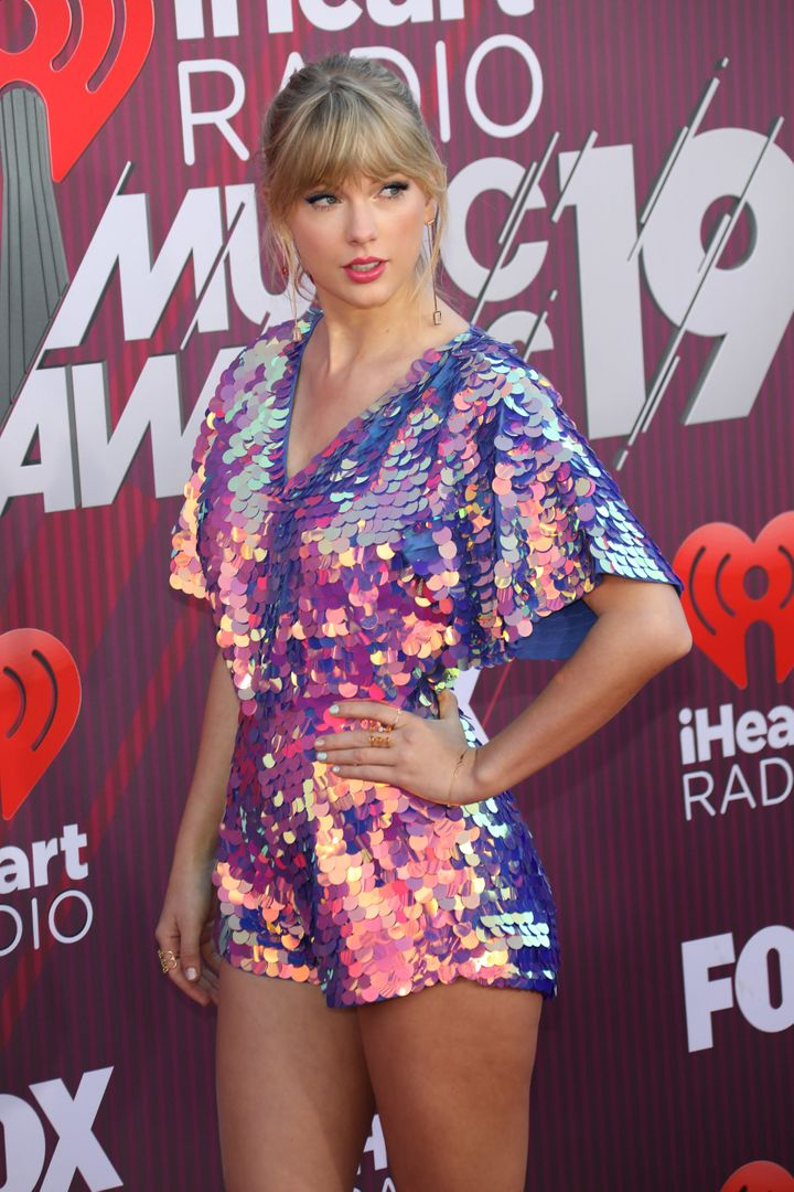"The hand-stitched romper featured ""iridescent sequins with flashes of purple, lilac, yellow and aqua,"" according to"