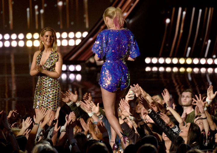 Maren Morris, left, presents Taylor Swift with the award for tour of the year at the iHeartRadio Music Awards.