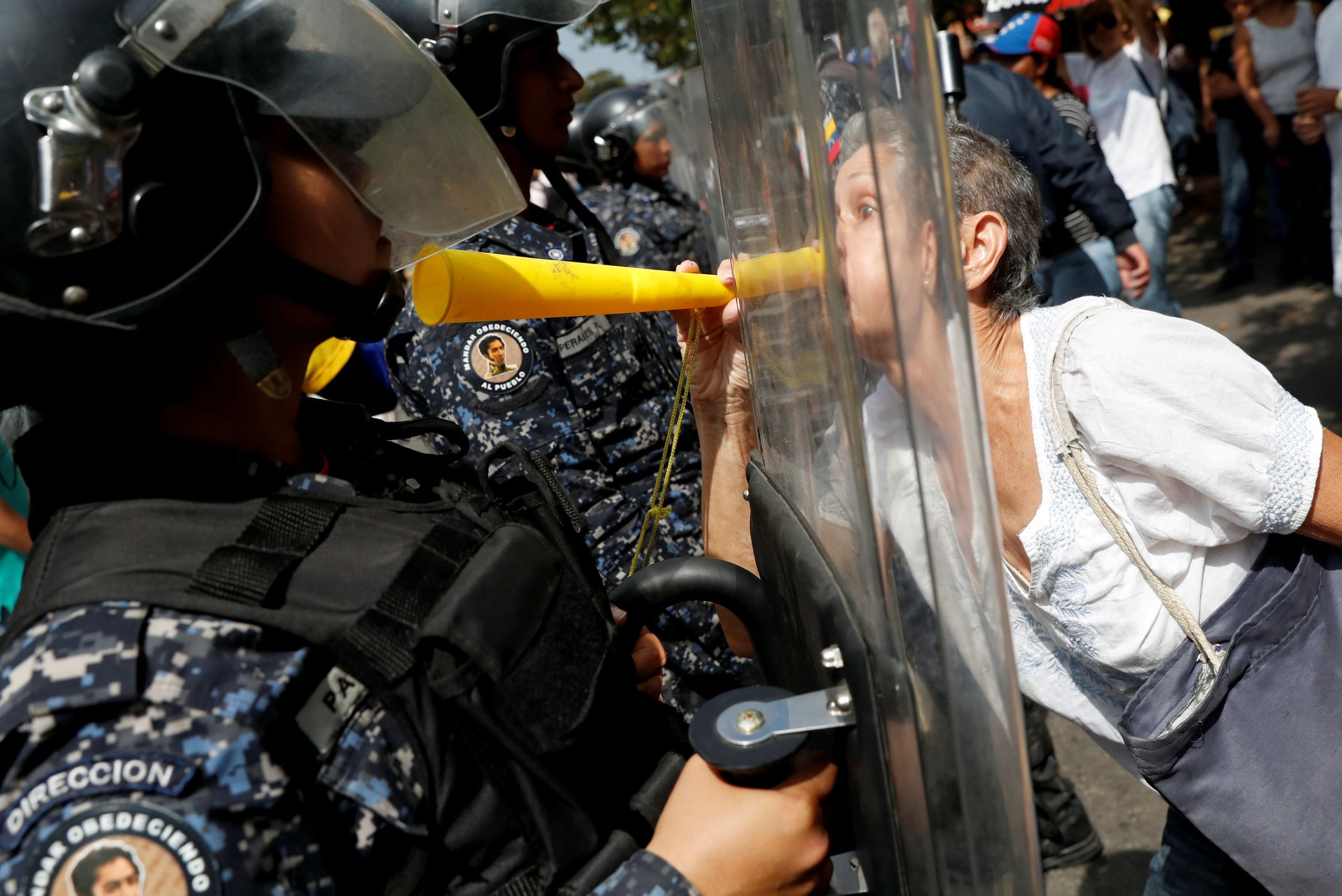 An opposition protester confronts a police officer at a rally against Venezuelan President Nicolás Maduro's government